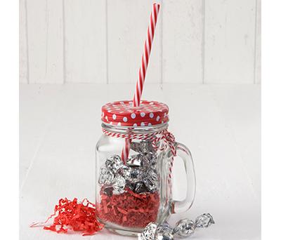 Tarro tapa roja topos y caña con chocolate como detalles para los invitados