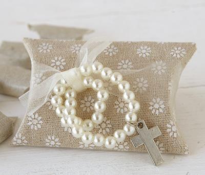 Estuche de tela con pulsera de perlitas y cruz con 5 caramelos como regalo para invitados de comunión