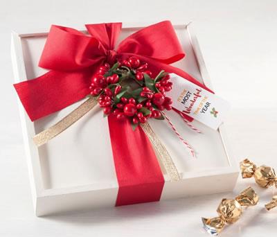 Caja de madera blanca con bombones crocki chock y decoración navideña para regalar