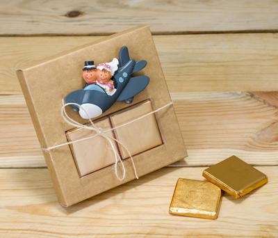 Novios en avión imán en caja kraft con napolitanas de chocolate como detalle para los invitados de la boda