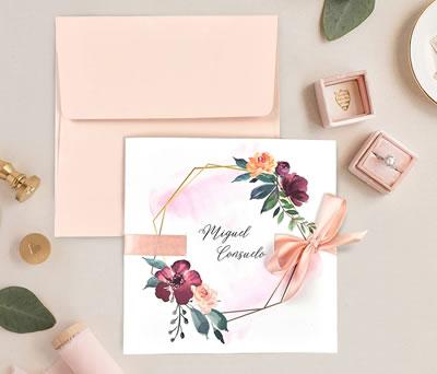 Invitación de boda con corona y adorno floral con lazo en color rosa con sobre a juego
